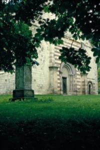 A templom bélletes kapuja és a jellegzetes, vöröses kövekből rakott homlokzati fal
